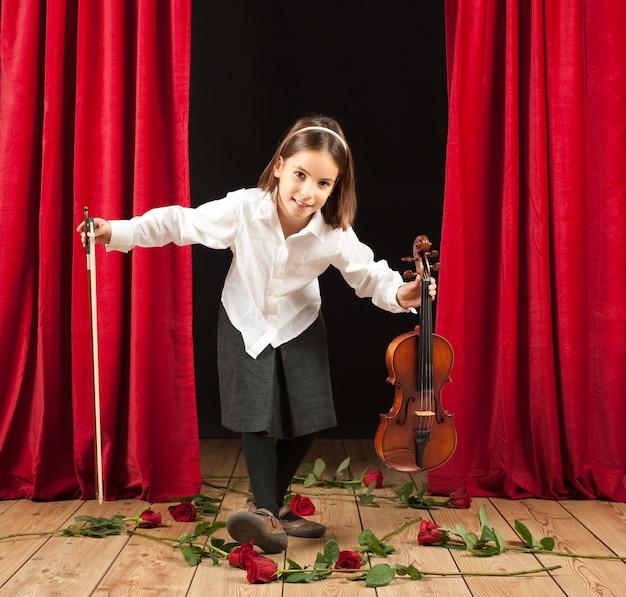 Kleines mädchen, das violine auf bühnentheater spielt