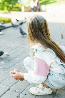 Kleines mädchen, das vögel in einem stadtpark füttert