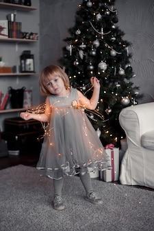 Kleines mädchen, das vor dem weihnachtsbaum steht und eine girlande in ihren händen hält