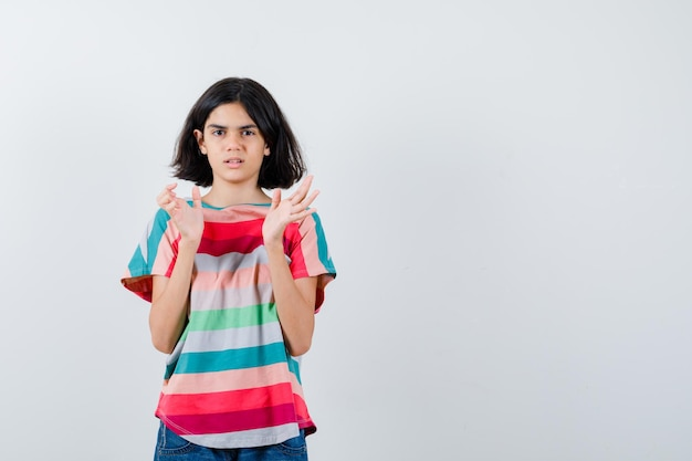 Kleines mädchen, das vorgibt, etwas im t-shirt zu fangen und verwirrt zu schauen. vorderansicht.