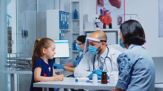 Kleines mädchen, das während der konsultation für covid-19 mit dem arzt spricht. kinderarzt, facharzt für medizin mit schutzmaske, der im krankenhauskabinett die behandlung von gesundheitsdienstleistungen anbietet