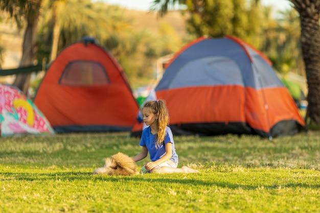 Kleines mädchen, das während einer wanderung mit einem welpen vor einem zelt spielt, das konzept der outdoor-aktivitäten und outdoor-abenteuer hochwertiges foto