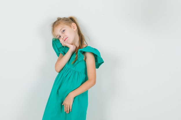 Kleines mädchen, das wange auf ihrer handfläche in der vorderansicht des grünen kleides lehnt.