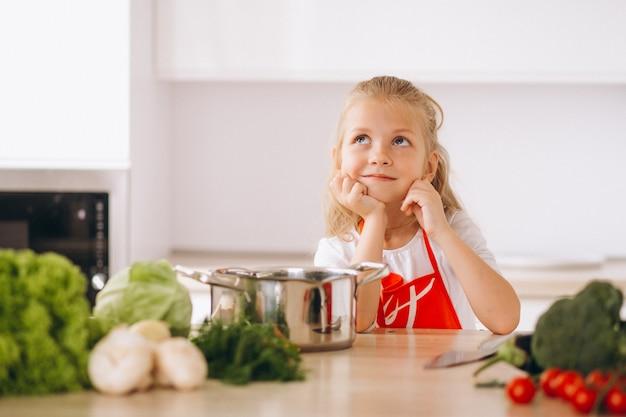 Kleines mädchen, das was denkt, an der küche zu kochen