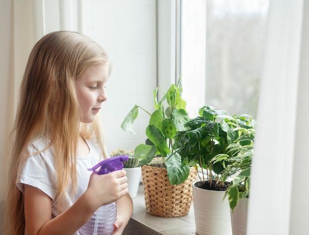 Kleines mädchen, das wasser auf zimmerpflanzen spritzt