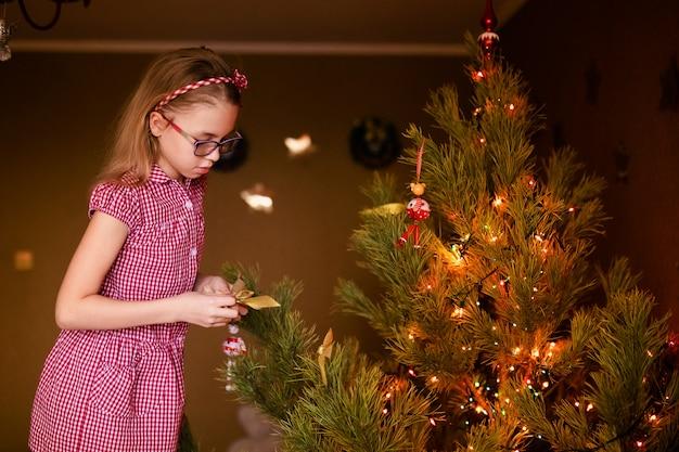 Kleines mädchen, das weihnachtsbaum mit spielwaren und flitter verziert
