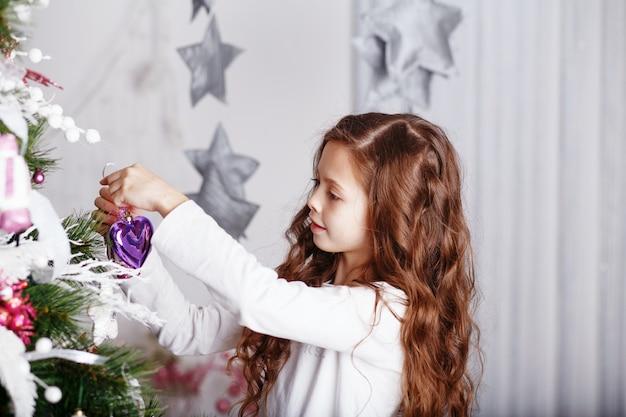 Kleines mädchen, das weihnachtsbaum mit spielzeug und blumen verziert