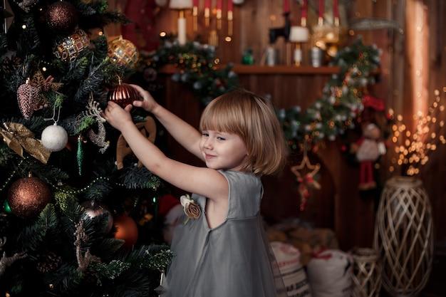 Kleines mädchen, das weihnachtsbaum mit verzierungen verziert und auf weihnachten wartet