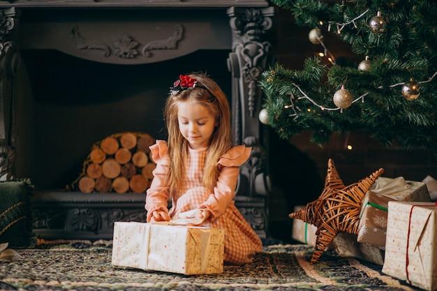 Kleines mädchen, das weihnachtsgeschenke durch weihnachtsbaum auspackt