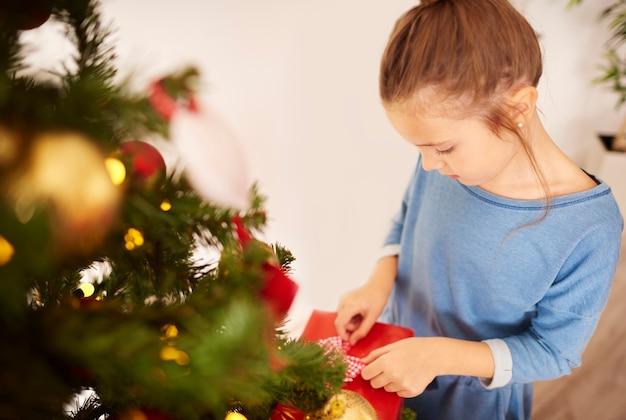 Kleines mädchen, das weihnachtsgeschenke vorbereitet