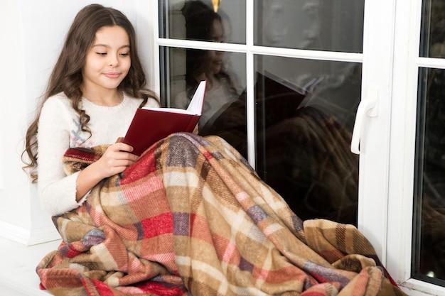 Kleines mädchen, das weihnachtsgeschichte liest. bestes weihnachtsbuch. buchhandlung kommerziell. kleines lächelndes kind las buch. literatur club. weihnachtsgeist. kleine leser genießen das lesen zu hause. silvester.