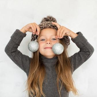 Kleines mädchen, das weihnachtskugeln nah an ihrem gesicht hält