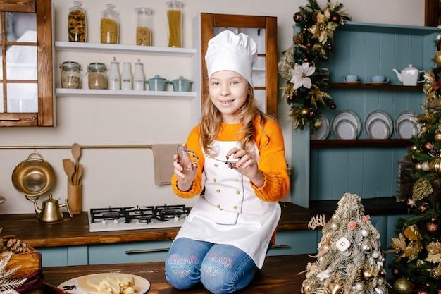 Kleines mädchen, das weihnachtslebkuchen an der küche im dekorierten wohnzimmer macht backen und kochen mit kindern für weihnachten zu hause