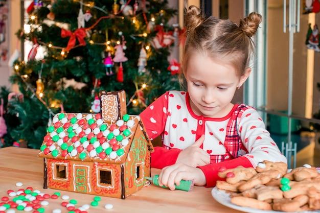 Kleines mädchen, das weihnachtslebkuchenhaus am kamin in verziertem wohnzimmer macht.