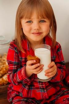 Kleines mädchen, das weihnachtsplätzchen isst und milch trinkt