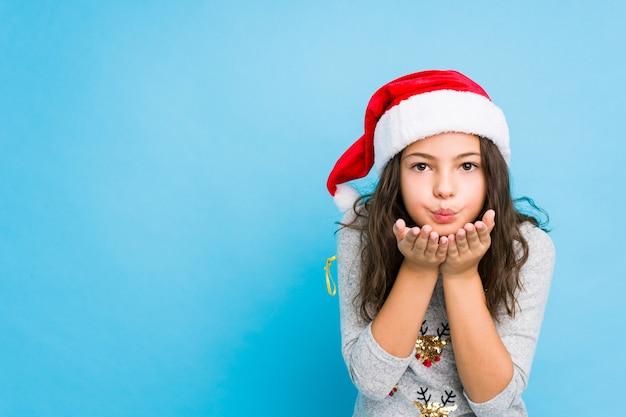 Kleines mädchen, das weihnachtstag faltende lippen feiert und palmen hält, um luftkuß zu senden.