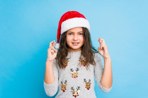 Kleines mädchen, das weihnachtstagüberfahrtfinger für das haben des glücks feiert
