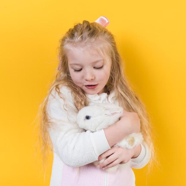Kleines mädchen, das weißes kaninchen betrachtet