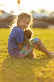Kleines mädchen, das welpenkind mit haustierhundefamilie und haustieren auf parkrasenkind hält und tierfreundschaft hochwertiges foto hält