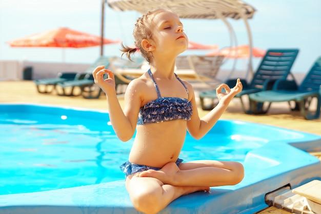 Kleines mädchen, das yoga am strand tut