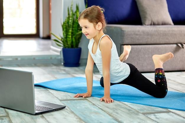 Kleines mädchen, das yoga, dehnen, fitness durch video auf notizbuch praktiziert.