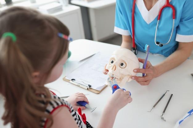 Kleines mädchen, das zahn mit medizinischen spielzeuginstrumenten auf astronomischem schädel bei zahnarztterminnahaufnahme herauszieht