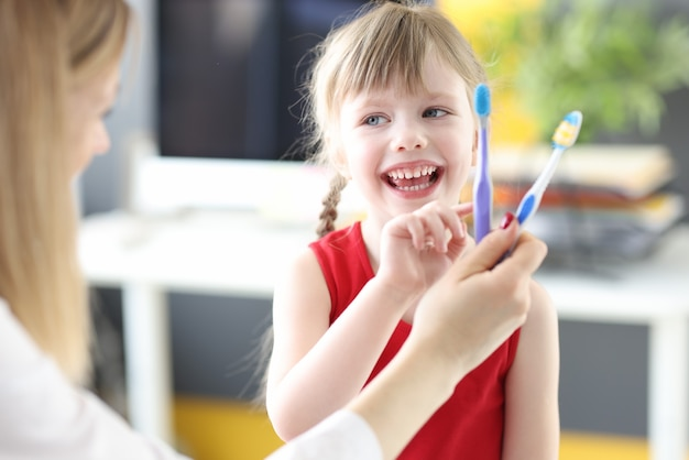 Kleines mädchen, das zahnbürste an der zahnarztpraxis wählt