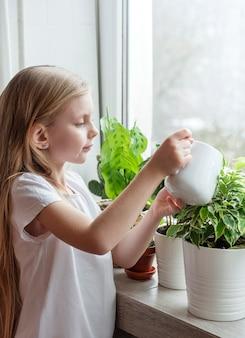 Kleines mädchen, das zimmerpflanzen in ihrem haus gießt
