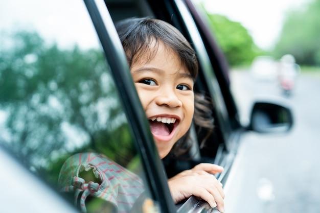 Kleines mädchen, das zu den fenstern schaut, öffnet mit lächeln
