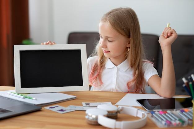 Kleines mädchen, das zu hause an online-kursen teilnimmt