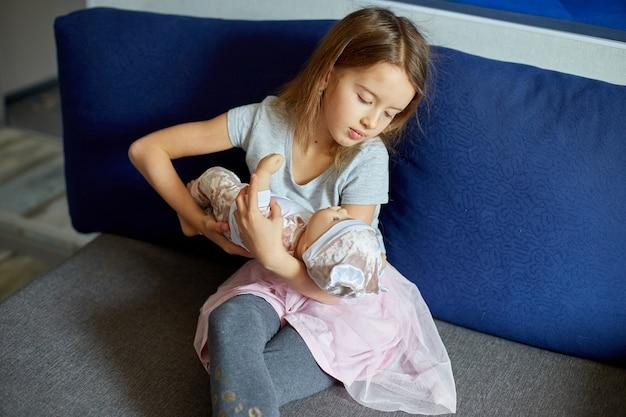 Kleines mädchen, das zu hause auf dem sofa im zimmer sitzt und mit babypuppe spielt, ein lied singt, wie mama.
