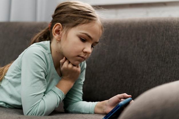 Kleines mädchen, das zu hause auf einem smartphone spielt