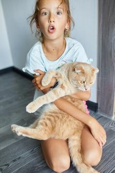 Kleines mädchen, das zu hause eine katze in den armen hält, kind, das mit haustieren spielt, liebenswürdiger freund.