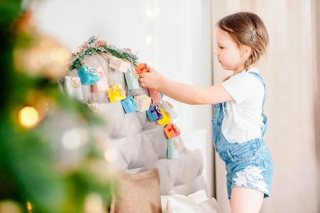 Kleines mädchen, das zu hause handgemachten adventskalender mit geschenkbox hält. diy adventskalender für kinder