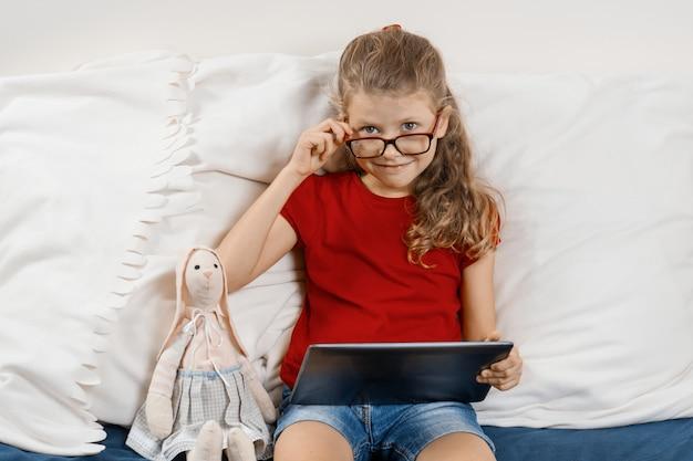Kleines mädchen, das zu hause im bett mit spielzeug und digitaler tablette sitzt