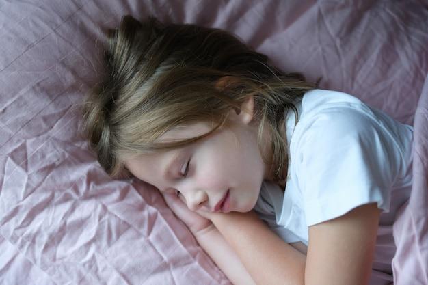 Kleines mädchen, das zu hause im rosa bett schläft