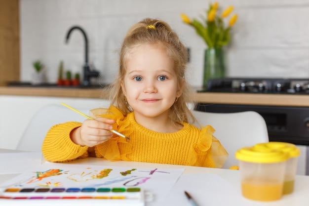 Kleines mädchen, das zu hause malt. lächelndes kind mit pinsel in den händen. frühkindliche bildung