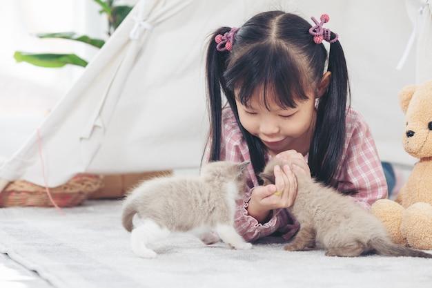 Kleines mädchen, das zu hause mit katze, freundschiffskonzept spielt.