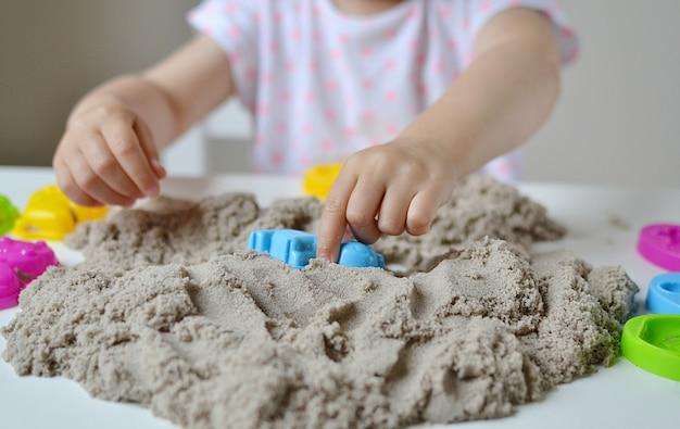 Kleines mädchen, das zu hause mit kinetischem sand plyaying ist