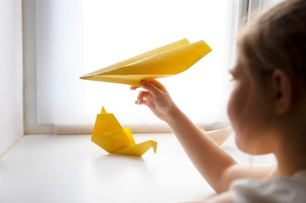Kleines mädchen, das zu hause mit origami-papier spielt