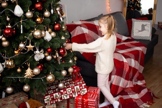 Kleines mädchen, das zu hause mit weihnachtsbaumdekoration spielt
