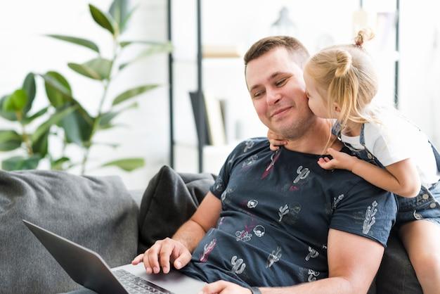 Kleines mädchen, das zu ihrem vater beim arbeiten an laptop küsst