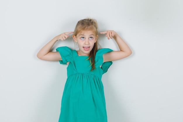 Kleines mädchen, das zunge mit fingergeste im grünen kleid zeigt