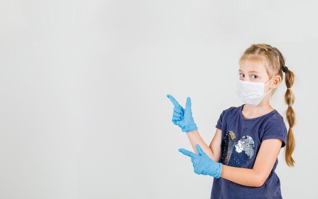 Kleines mädchen, das zwei finger zeigt kamera in t-shirt, handschuhen und maske vorderansicht.
