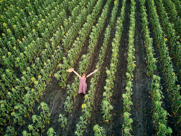 Kleines mädchen, das zwischen dem sonnenblumenfeld steht, mit beiden händen in der luftaufnahme erhoben