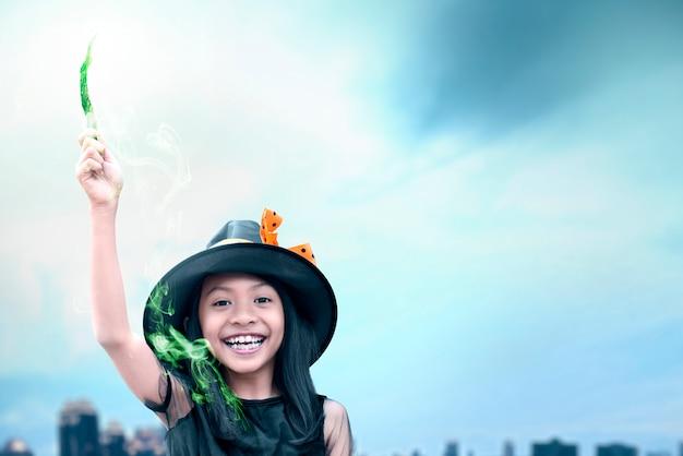 Kleines mädchen der asiatischen hexe, das den stab mit einem magischen glanz verwendet