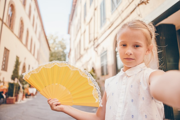 Kleines mädchen der entzückenden mode draußen in der europäischen stadt