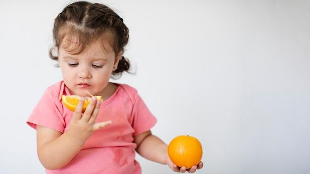 Kleines mädchen der nahaufnahme, das ihre orangen betrachtet