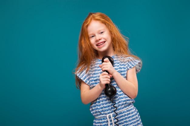 Kleines mädchen der netten schönheit im t-shirt mit dem langen haar sprechen ein telefon