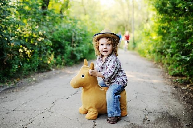 Kleines mädchen der rothaarigen, das ein spielzeugpferd reitet.